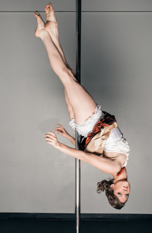 teacher in an inverted leg hold on the pole