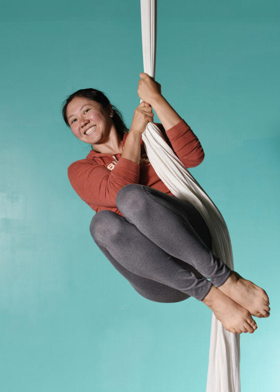 an aerialist tucks in the air on aerial silks