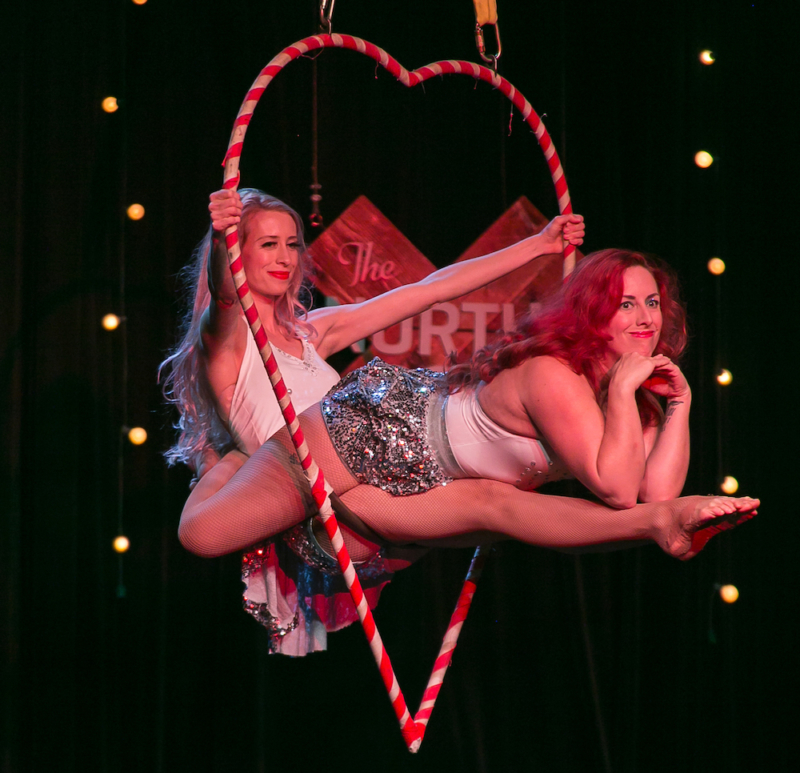 two aerial performers pose in a heart-shaped lyra