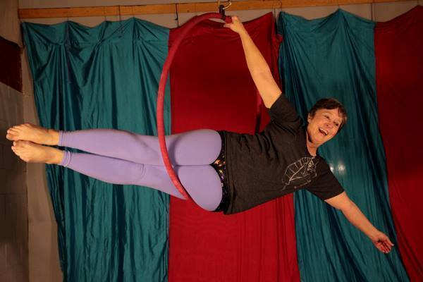 student performs aerial move in lyra