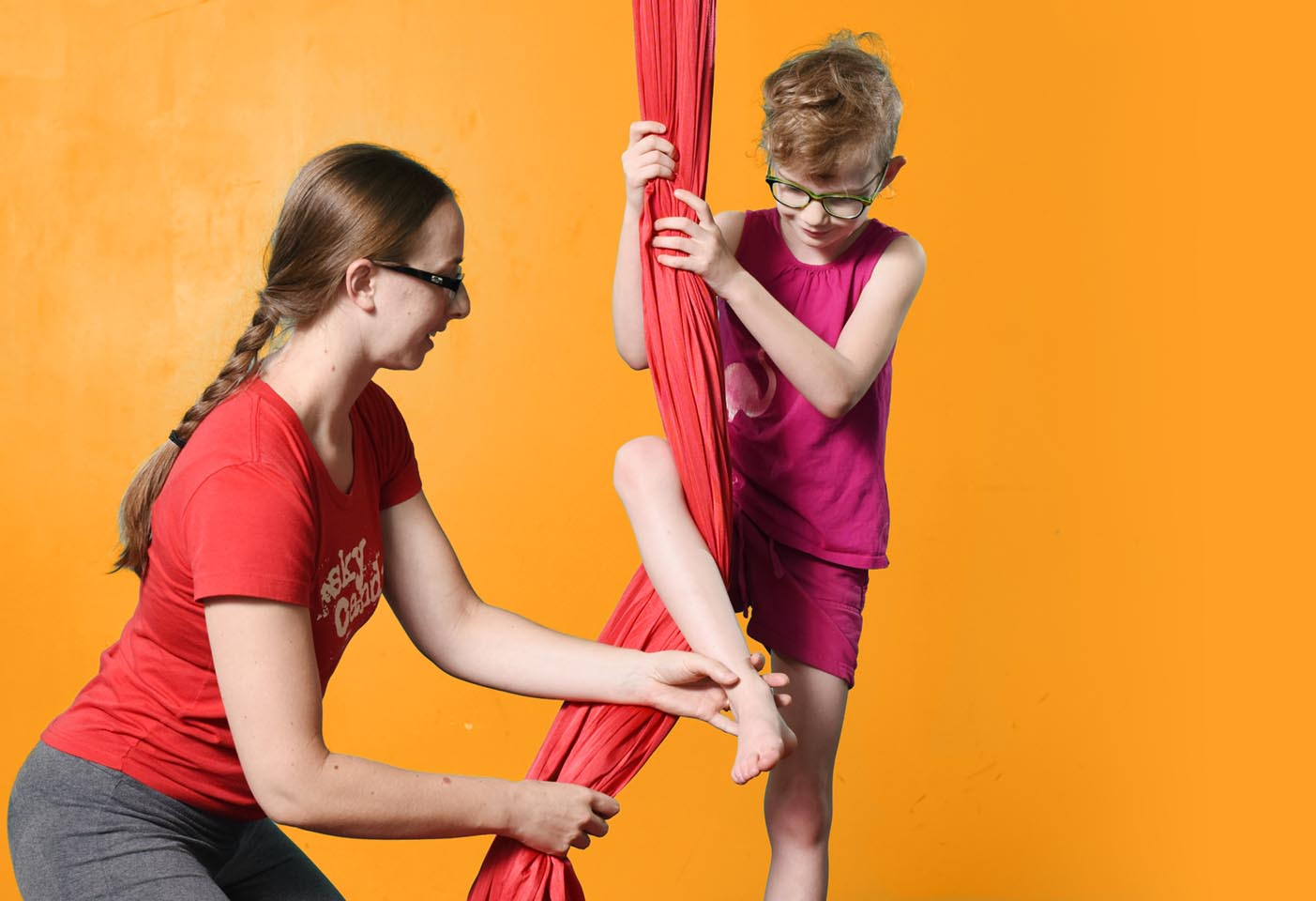 female teacher helping child on aerial silks
