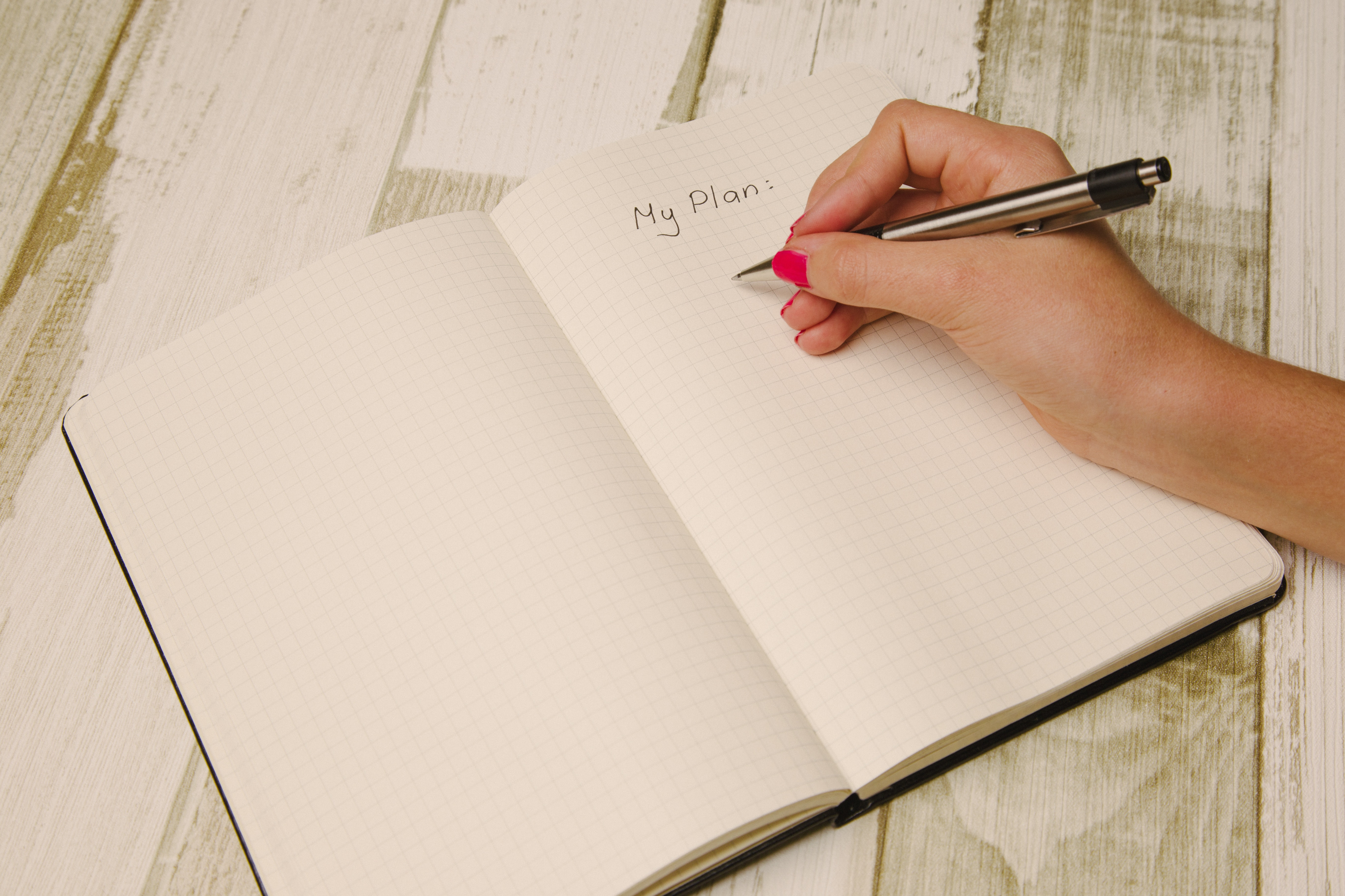 female hand writes a plan in a gridded journal