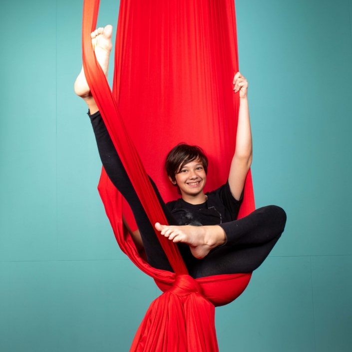 youth student strikes a pose in an aerial hammock