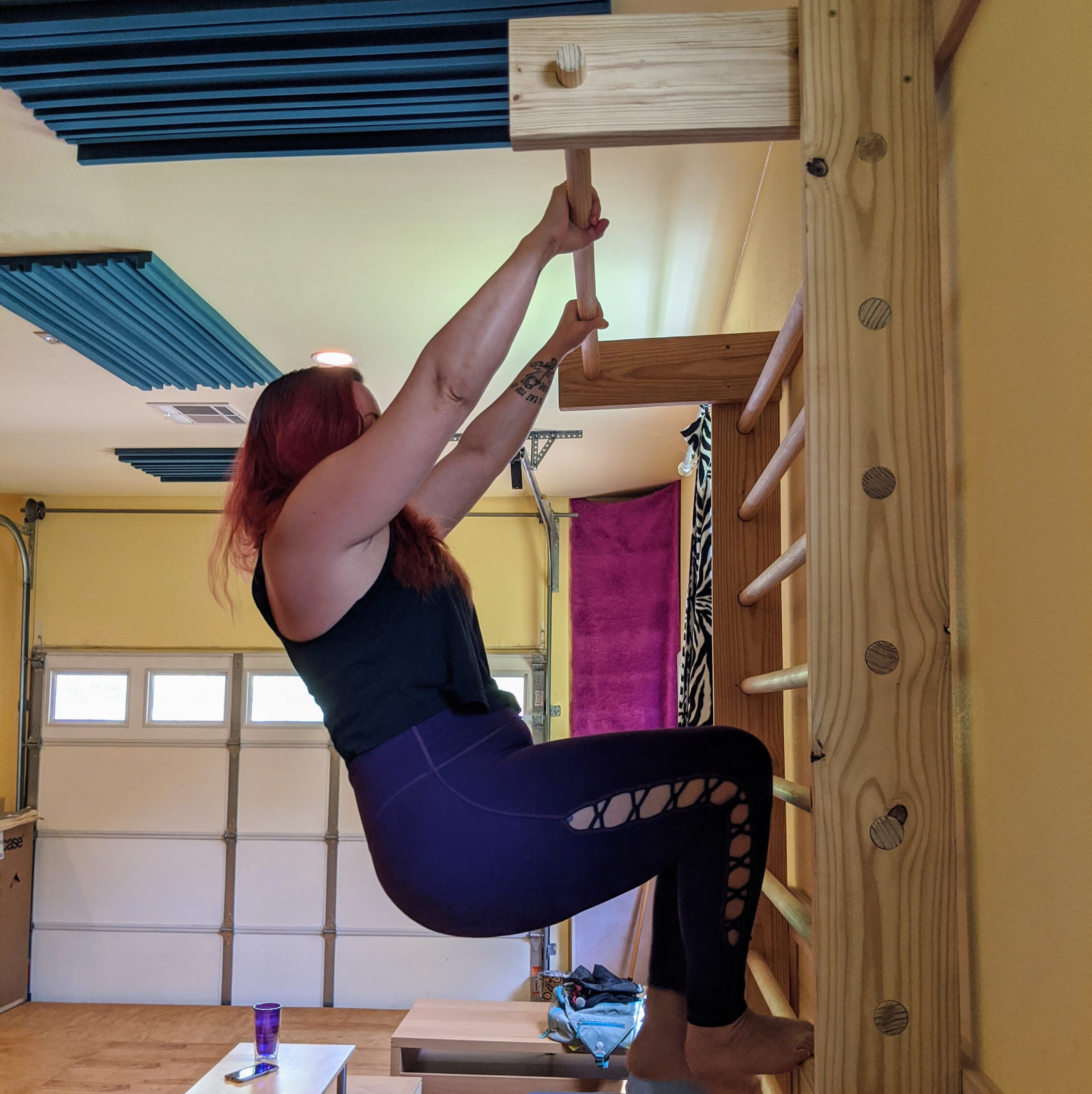 woman doing pull-ups on a set of stall bars in her home gym